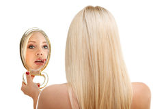 Young woman checking her hair in mirror Stock Photo