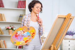 Young woman is checking her piece of art Stock Image