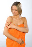 Young woman checking her skin. Young woman wearing orange towel checking her skin Royalty Free Stock Images