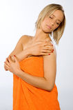 Young woman checking her skin. Young woman wearing orange towel checking her skin Royalty Free Stock Photos