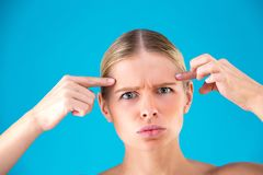 Young Woman checking her wrinkles on her forehead - isolated on blue background stock photography