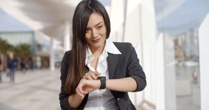 Young woman checking her wristwatch for the time Stock Photos