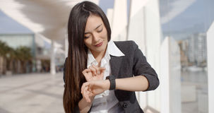Young woman checking her wristwatch for the time Stock Photo