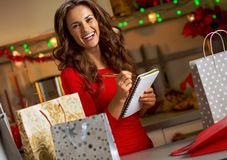 Young woman checking list of christmas presents Royalty Free Stock Photos