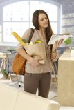 Young woman checking mail upon arrival at home. Young woman arriving at home, checking mail, holding shopping bag Royalty Free Stock Photo