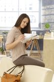 Young woman checking mail as getting home. Young woman sitting on backrest of sofa, checking mail as arriving at home royalty free stock photography