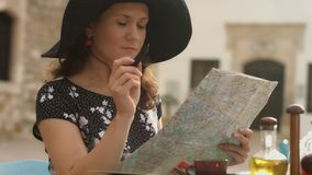 Young woman checking map, satisfied with journey plan, making notes with pen. Stock footage stock video