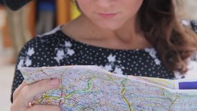 Young woman checking map, searching route for sightseeing tour, planning trip. Stock footage stock video footage