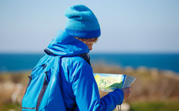 Young woman checking map in seashore on hiking trip. Stock Image