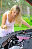 Young woman checking oil level in the car Royalty Free Stock Photo