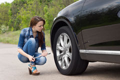 Young woman checking out a flat tyre on her car Royalty Free Stock Photo