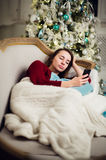 Young woman checking out her text messages on mobile phone as she liyng sofa in front of the Christmas tree at home. Young woman checking out her text messages Stock Images