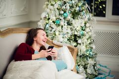Young woman checking out her text messages on mobile phone as she liyng sofa in front of the Christmas tree at home. Young woman checking out her text messages Stock Photography