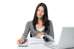 Young woman checking a report or invoices. In a large office binder doing manual calculations to verify the figures on a desktop calculator Stock Images