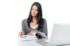 Young woman checking a report or invoices. In a large office binder doing manual calculations to verify the figures on a desktop calculator Stock Photography