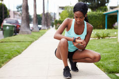 Young woman checking smart watch in the street before a run Stock Image