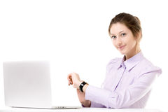 Young woman checking time in front of laptop Stock Photography