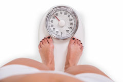 Young Woman Checking Weight Over White Background royalty free stock images