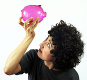 Young woman checks empty piggy bank Royalty Free Stock Photos