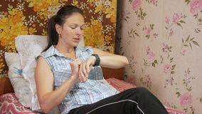 Young woman checks the messages on the smartwatch at home on the couch. stock video