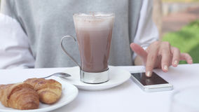Young woman checks notifications on smartphone and drinking cacao with croissant Royalty Free Stock Photos