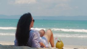 Young woman or a cheerful girl, sunbathing on the beach, enjoying the ocean, drinking coconut in the Sun, relaxing on a. Tropical beach. Concept of travel, sea stock footage