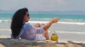 Young woman or a cheerful girl, sunbathing on the beach, enjoying the ocean, drinking coconut in the Sun, relaxing on a. Tropical beach. Concept of travel, sea stock video footage