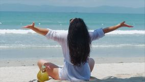 Young woman or a cheerful girl, sunbathing on the beach, enjoying the ocean, drinking coconut in the Sun, relaxing on a. Tropical beach. Concept of travel, sea stock video