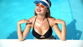 Young woman cheerfully smiling and relaxing in swimming pool, summer days. Stock photo stock photo