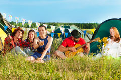 Young woman cheering at camping among her friends. Happy young women holding glass of beer at camping among her friends, sitting on grass stock photos