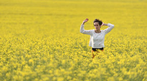 Young woman cheering in canola field in the summer Royalty Free Stock Photo