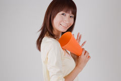 Young woman cheering with megaphone. Young Asian woman cheering with megaphone Stock Photo