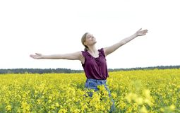 Woman cheering in the rape field. Young woman cheering in the rape field Royalty Free Stock Image