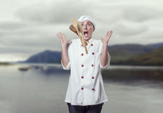 Young woman chef astonished with her wood utensils flying Stock Photo