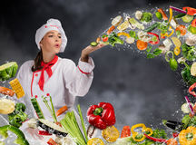 Young woman chef blowing fresh vegetable. In water splashes. Concept of food preparation royalty free stock images