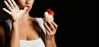 Young woman chef cook hold sweet cup cake with cream strawberry lick finger on black stock images