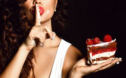 Young woman chef cook holding sweet piece cake with strawberry blueberry and cream show quiet shhh sign royalty free stock photos