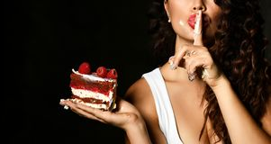 Young woman chef cook holding sweet piece cake with strawberry blueberry and cream show quiet shhh sign stock photos