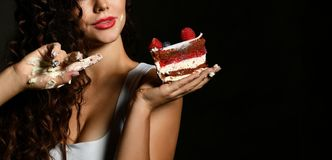 Young woman chef cook holding sweet piece cake with strawberry blueberry and cream smiling on black royalty free stock photography