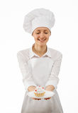 Young woman chef cook showing cake Royalty Free Stock Photos