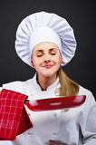 Young woman chef with different tools on dark background Stock Image