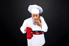 Young woman chef with different tools on dark background Royalty Free Stock Photos