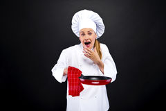 Young woman chef with different tools on dark background Stock Photo