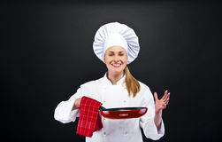 Young woman chef with different tools on dark background Stock Images