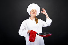 Young woman chef with different tools on dark background Royalty Free Stock Images
