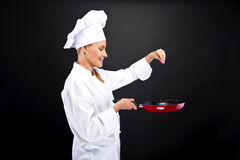 Young woman chef with different tools on dark background Royalty Free Stock Photo