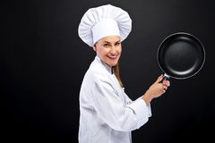 Young woman chef with frying pan on dark background Royalty Free Stock Images