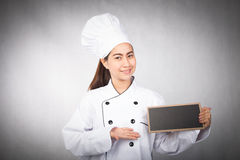 Young woman chef holding black board Stock Photos