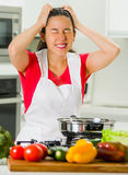 Young woman chef holding hair in frustration, discouraged facial expression, table with kettle and vegetables.  Stock Photo