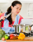 Young woman chef holding knife and looking into kettle of cooking food with skeptical facial expression Royalty Free Stock Photos